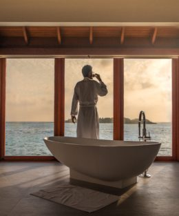 Man looking out to sunset, dressed in a luxurious bathrobe and beside a spectacular bath, after getting up from bed to have a cup of tea or coffee.