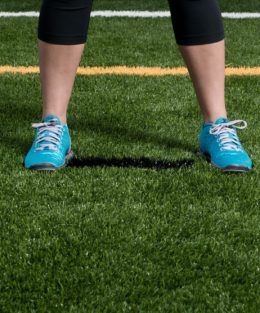 Person standing in blue trainers on NFL pitch